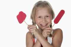Girl (10-11) holding lollypops, smiling, portrait Stock Photos