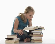 Portrait of a girl (10-11) reading in book - stock photo