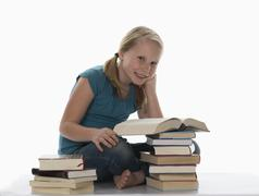 Portrait of a girl (10-11) and stacked books - stock photo