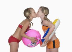Two girls (10-11) kissing, side view, portrait Stock Photos
