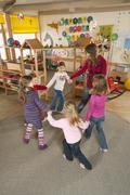 Germany, Nursery, Female nursery teacher and children dancing - stock photo