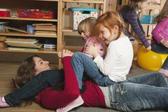 Germany, Nursery, Female nursery teacher and children playing together - stock photo