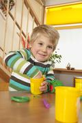 Germany, Boy (3-4) in nursery playing with modeling clay, smiling, portrait Stock Photos