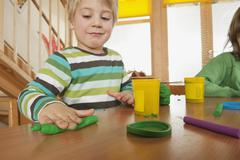 Germany, Two boys (3-4), (6-7) playing with modeling clay, portrait - stock photo