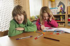 Germany, Boy (6-7) and girl (4-5) in nursery boy sticking out tongue, portrait Stock Photos
