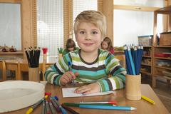 Stock Photo of Germany, Children in nursery, boy (4-5) in foreground holding felt-tip pen,