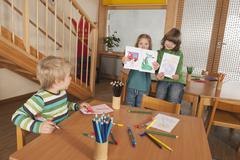 Stock Photo of Germany, Children in nursery, girls (4-5), (6-7) in background holding
