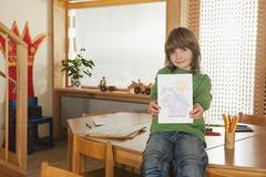 Germany, Boy (6-7) in nursery hoding painting, smiling, portrait - stock photo