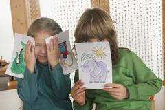 Stock Photo of Germany, Boy (6-7) and girl (4-5) in nursery covering faces with paintings,