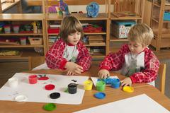Germany, Two boys (3-4), (6-7) fingerpainting in nursery - stock photo