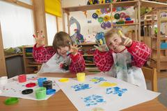 Germany, Two boys (3-4), (6-7) fingerpainting in nursery, showing hands, - stock photo