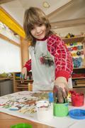 Germany, Boy (6-7) fingerpainting in nursery, portrait - stock photo