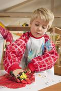 Germany, Boys  (3-4) fingerpainting in nursery - stock photo