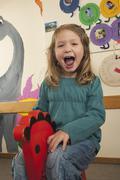 Germany, Girl (4-5) sitting on rocking horse, portrait Stock Photos