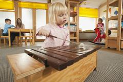 Stock Photo of Germany, Girl (3-4) playing xylophone, Female nursery teacher with children in