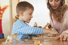 Germany, Female nursery teacher and boy (4-5) doing jigsaw puzzle, portrait - stock photo