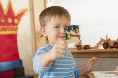 Stock Photo of Germany, Boy (4-5) in nursery holding piece of a puzzle, portrait