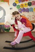 Germany, Girl (3-4) sitting on rocking horse, holding teddy, portrait Stock Photos