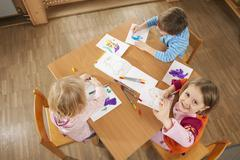 Germany, Children in nursery sitting at table drawing pictures, elevated view Stock Photos