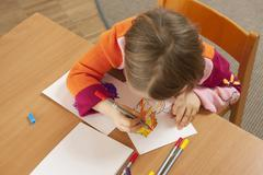 Germany, Girl (3-4) in nursery drawing a picture, elevated view Stock Photos