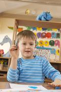 Stock Photo of Germany, Boy (4-5) in nursery holding felt-tip pen, portrait