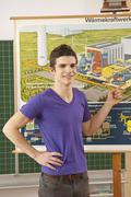 Germany, Emmering, Teenage boy pointing on chart, smiling, portrait - stock photo