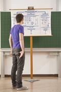 Germany, Emmering, Teenage boy watching at chart with hands in pocket - stock photo