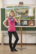 Stock Photo of Germany, Emmering, Young woman pointing on chart, smiling, portrait
