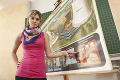 Stock Photo of Germany, Emmering, Young woman pointing on chart, portrait