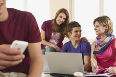 Germany, Emmering, Students using laptop with man holding mobile in foreground - stock photo