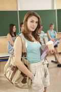 Germany, Emmering, Teenage girl smiling with students in background Stock Photos