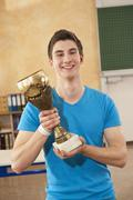 Germany, Emmering, Teenage boy holding trophy, smiling, portrait Stock Photos
