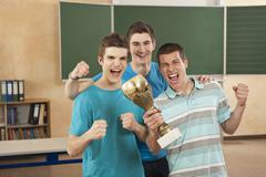 Germany, Emmering, Friends holding trophy and clenching fist, smiling Stock Photos