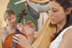 Germany, Emmering, Young women playing musical instruments - stock photo