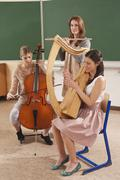 Germany, Emmering, Teenage girl and young women playing musical instruments - stock photo