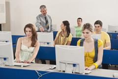Germany, Emmering, Lecturer training students in computer lab - stock photo