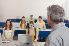 Germany, Emmering, Lecturer watching, students using computer in computer lab Stock Photos