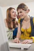 Germany, Emmering, Teenage girl whispering into woman's ear Stock Photos