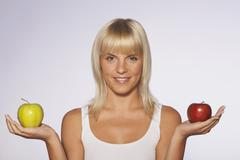 Stock Photo of Young woman with apples, smiling, portrait