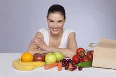 Young woman sitting with fruits and vegetables, smiling, portrait Stock Photos