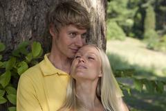 Germany, Dortmund, Young man looking away with woman eyes closed Stock Photos