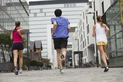 Stock Photo of Germany, Cologne, Young man and women jogging