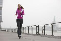Stock Photo of Germany, Cologne, Young woman jogging