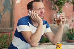 Young man talking on cellphone and drink beer in cafe NTSC - stock footage