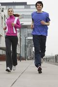 Stock Photo of Germany, Cologne, Young man and woman jogging