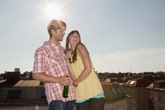 Germany, Bavaria, Munich, Young couple enjoying beer on rooftop Stock Photos