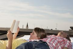 Stock Photo of Germany, Bavaria, Munich, Young couple relaxing on rooftop