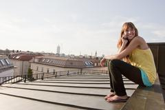Stock Photo of Germany, Bavaria, Munich, Young woman on the phone, smiling