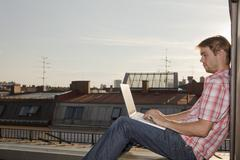 Stock Photo of Germany, Bavaria, Munich, Young man with laptop on rooftop