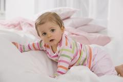 Baby girl (6-11 months) crawling on blanket - stock photo